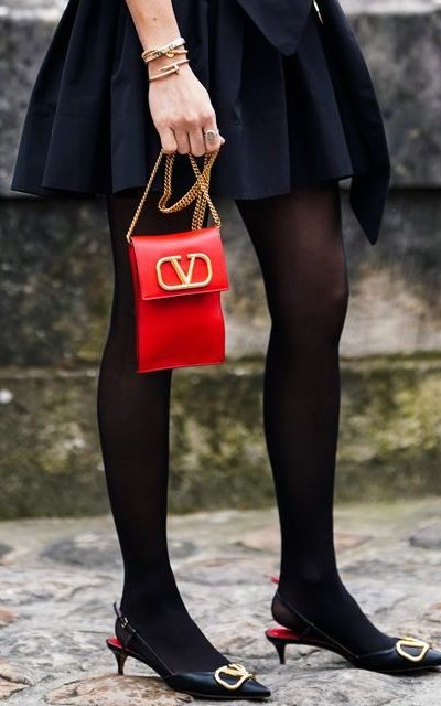 Woman in black pantyhose with red handbag and black dress